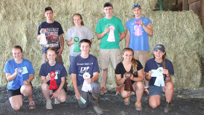 Winners pose in front of hay bales