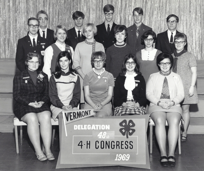 Circa 1969 black & white photo of folks with plastic glasses and women in short skirts sitting in chairs.