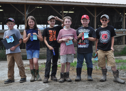 group of children with ribbons and awards in front of barn