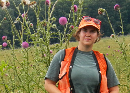 Alea Tuttle standing in a North Carolina pasture next to an introduced invasive called