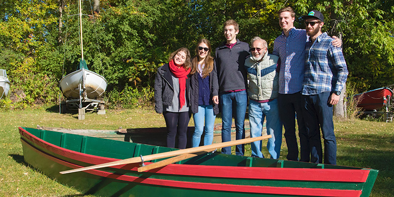 Charlie Auer and students stand behind skiff