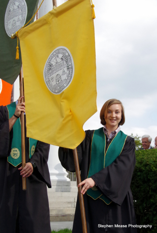 Student carries the gold banner of CALS