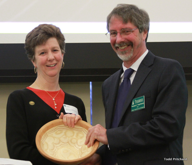 Two people holding wooden bowl award