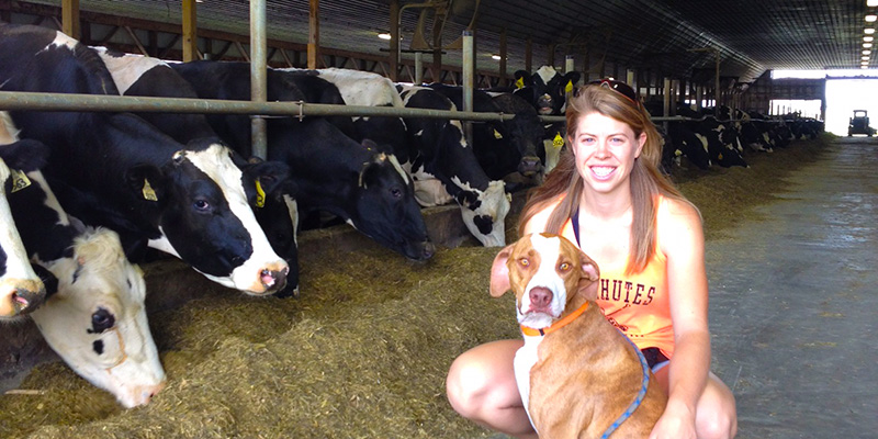 Courtney Hammond Wagner with cows and dog.