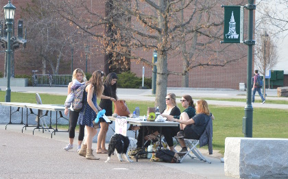 Students talk to passerby with dog outside of the Davis Center at UVM