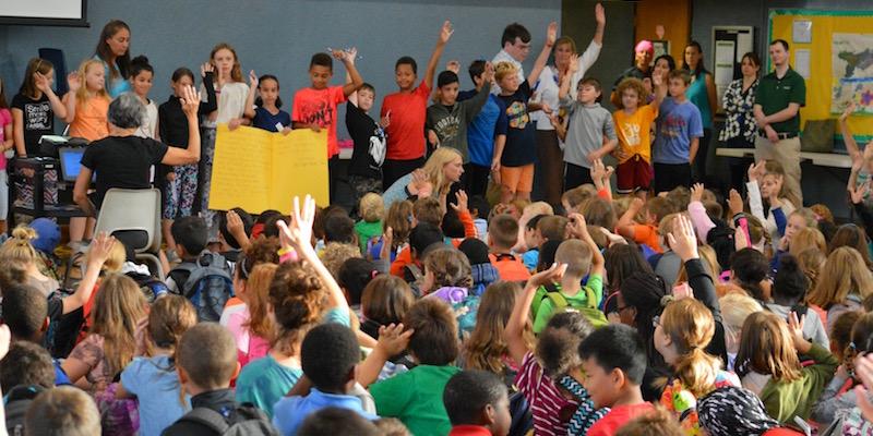 Children in a school raising hands