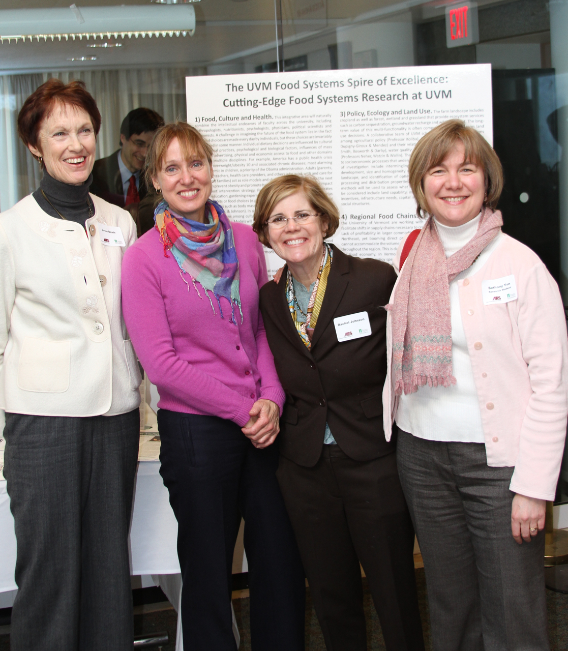 Four researchers smile in front of their display.