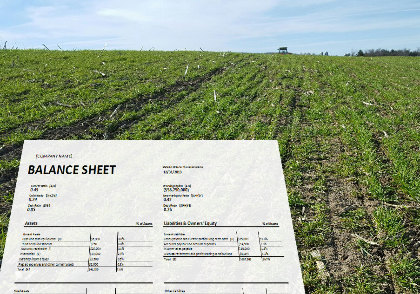 Field with balance sheet in foreground