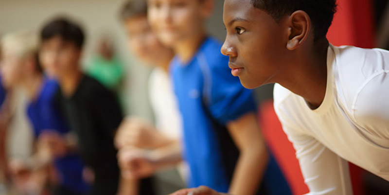 A participant in the NFL's PLAY 60 program prepares to take off at the start of a running event.