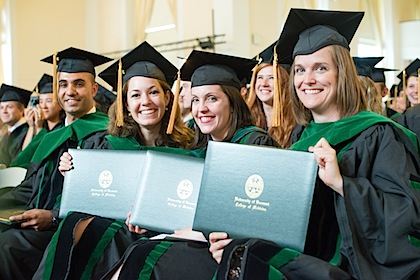College of Medicine Class of 2013 members holding their newly-bestowed diplomas at  Commencement in May.