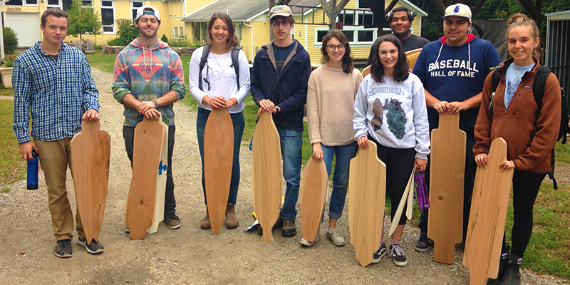 Group of students holding wooden longboards