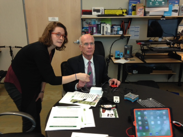 Tracy Roux teaching the Congressman how to navigate an iPad with assistive technology devices