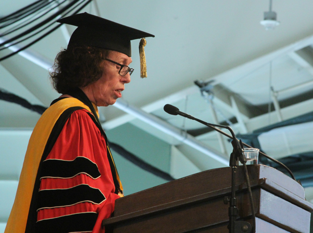 Susan Wallace in cap and gown, speaking.