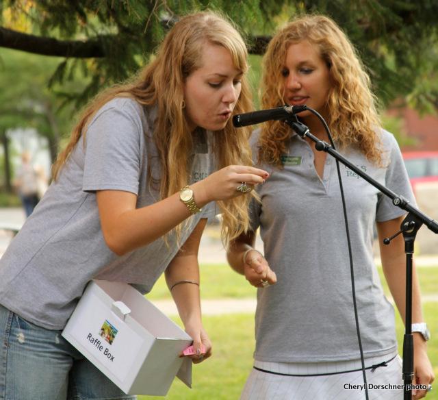 Two women read raffle winners' numbers.
