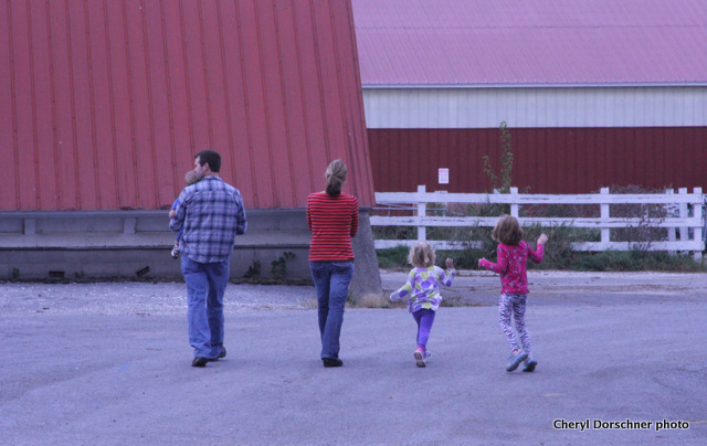 Family strolling among barns.