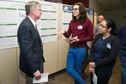 Sonam Kapadia and Brenton Nash, both members of the UVM College of Medicine Class of 2016, discuss their public health project with Bill Jeffries, M.D., senior associate dean for medical education, during the tenth annual Public Health Project Poster Session and Celebration.