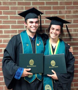 Two dark-haired grinning sibs in black and green caps and gowns and holding diplomas.