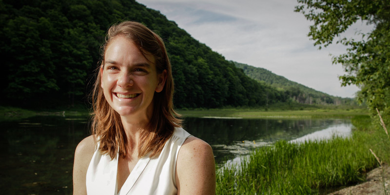 A photo of UVM PhD student Keri Bryan Watson, who led the first study to calculate the economic value of river wetlands and floodplains during Tropical Storm Irene and other flood events that have struck the U.S. East Coast in recent years. The photo shows Watson smiling, standing on a floodplain in Vermont. Photo by Will Watson.