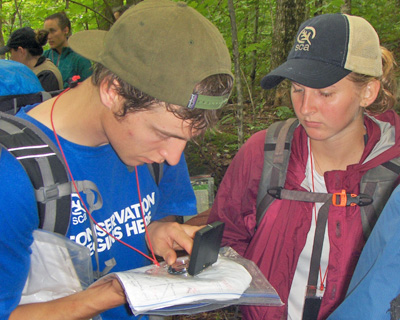 From left: Kristian Moore (ENVS '14) and Sam Smith (NR '14) navigate to a Concord Woods Natural Area property corner using map and compass.