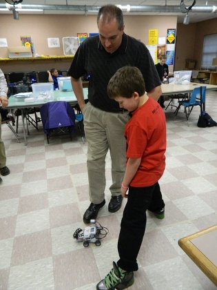 teacher and child watching 4-wheel robot
