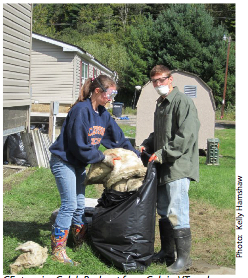 Students with respirators cleaning up mobile home park.