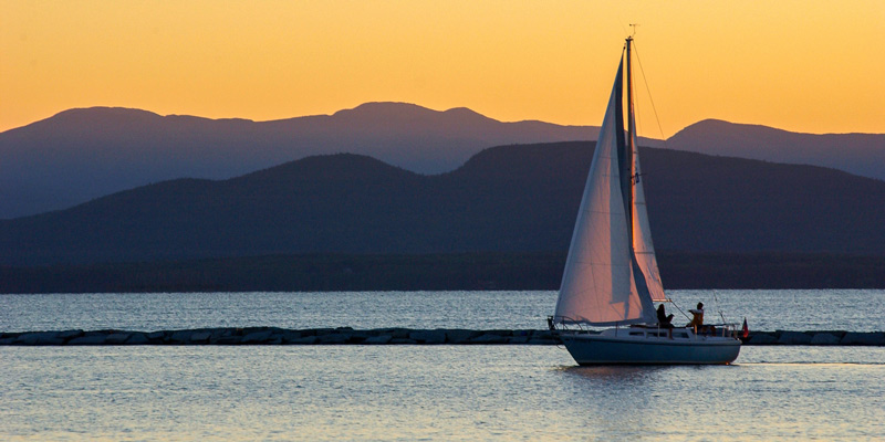 An image of a sailboat on Vermont's Lake Champlain at sunset. The visual appearance of Lake Champlain – specifically, how clean its water looks – has a major effect on the state economy, a new UVM study finds. The research was made possible with support from the Lake Champlain Basin Program. Photo: Sally McCay.