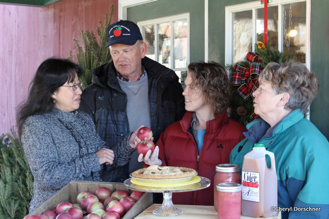 Adams family of apple growers and Liang talk about their products in hand: apples, pie, applesauce and cider.