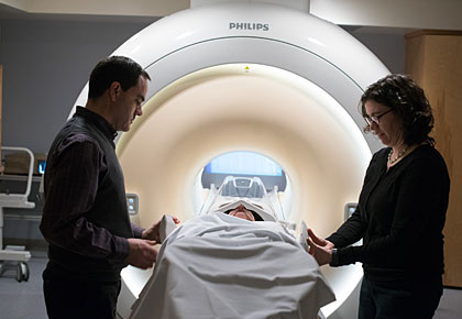 Jay Gonyea, administrator of the MRI Center for Biomedical Imaging, and Associate Professor of Psychiatry Julie Dumas, Ph.D., prepare a research subject in front of the circular magnet of the MRI.