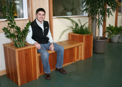 Matthew Durfee (PRT '12) and his custom built planter box-bench made from reclaimed Aiken Center furniture