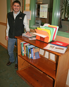 Matt and his custom built bookcase constructed from old classroom chairs and shelving