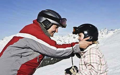 Parent and child wearing helmets on ski slope