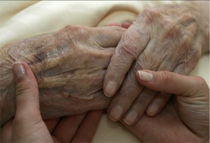 Young and elderly hands clasped
