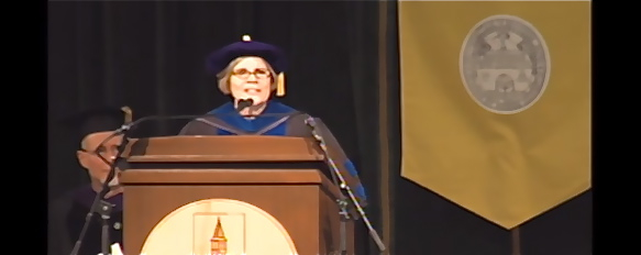 Speaker in regalia at podium. Yellow banner on the right.