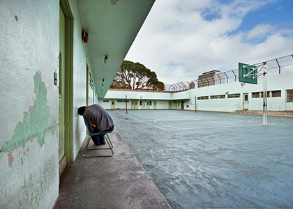child with back turned and head against the wall at Hale Ho'omalu Juvenile Hall, Oahu, Hawaii.