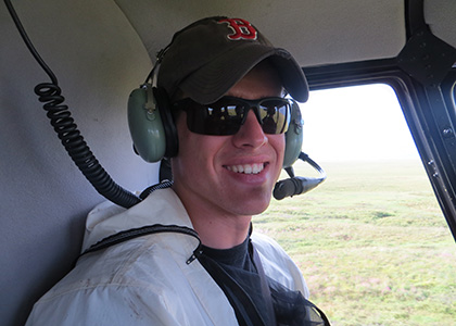 Ryan Sleeper rides in helicopter over Alaskan tundra.