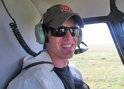 Ryan Sleeper inside an R-44 helicopter over the Alaskan tundra