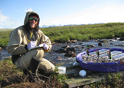 Sam Parker conducting stream research in Alaska.