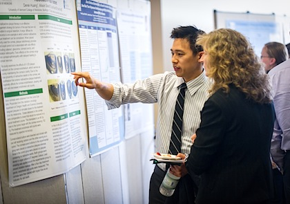 Derek Huang, M.D.'12 explains his research poster during a previous scholarly projects presentation by senior medical students.