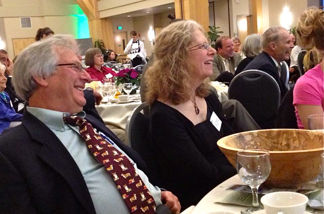 Smiling couple in crowd at dinner.
