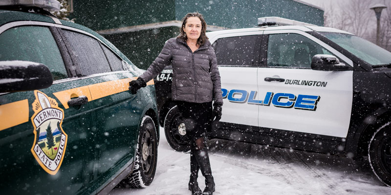 UVM's Stephanie Seguino is photographed between two police cars on a Vermont snowy day.