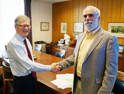 UVM College of Medicine Dean Frederick C. Morin III, M.D., left, shakes hands with Vermont Oxford Network Chief Executive and Scientific Officer and Lucey Chair in Neonatal Medicine Jeffrey Horbar, M.D. (Photo: COM Design & Photography).