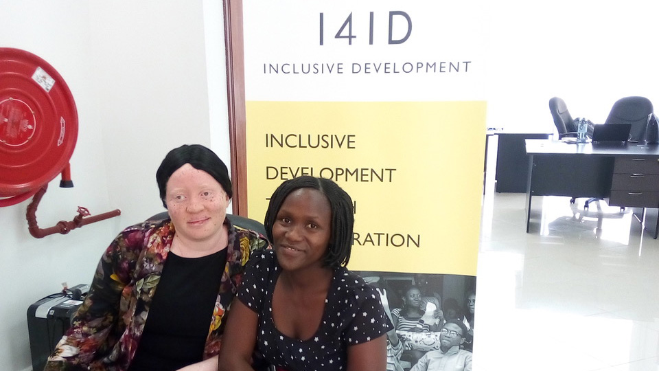 Catherine and Victoria in front of a I4ID sign
