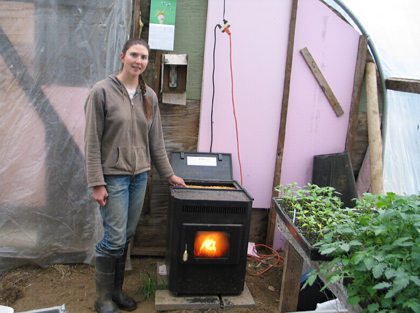 woman standing next to corn stove in greenhouse