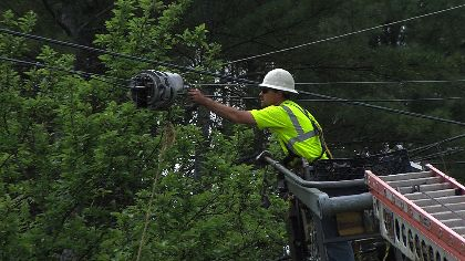 Utility worker installing fiber optic cable