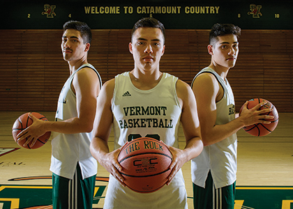 Everett, Ernie, and Robin Duncan all holding basketballs on the court.