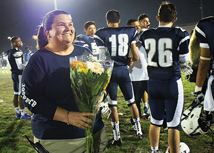 Kristin farrell holding roses at a high school football