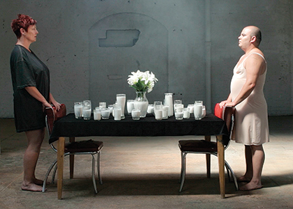 Still from Kairos Dirt and the Errant Vacuum film, two people standing at a table covered with glasses of milk
