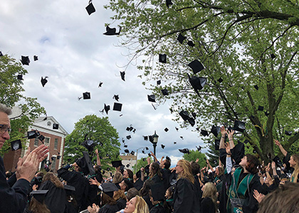2018 graduates tossing their caps into the air on the green at the end of commencement
