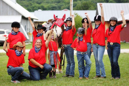 Members of the club dressed in red shirts and jeans pose with their horse