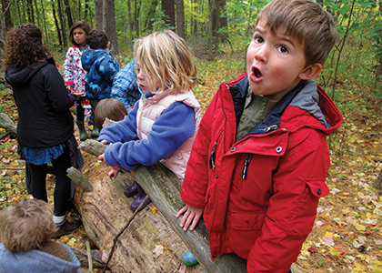 children from the UVM children's center playing in the woods.